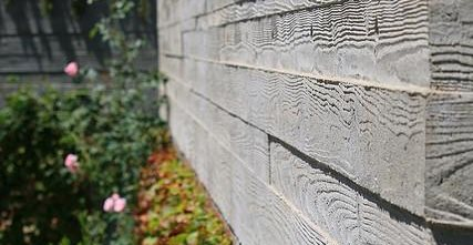 close-up of board formed concrete wall bordering a garden.